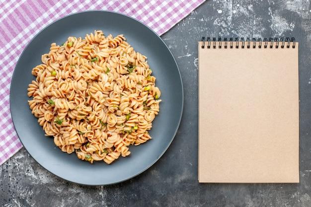 Vista superior da massa rotini em prato redondo em caderno de toalha de mesa quadriculada rosa branca em superfície escura Foto gratuita