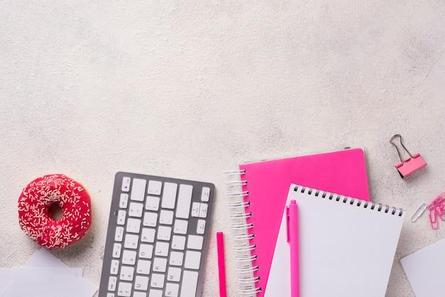 Vista superior da mesa com cadernos e rosquinhas Foto gratuita