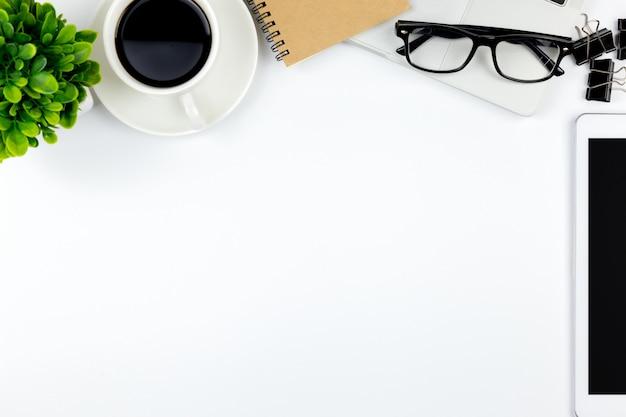 Vista superior da mesa de escritório com espaço de trabalho no escritório com tablet notebook em branco e smartphone Foto Premium