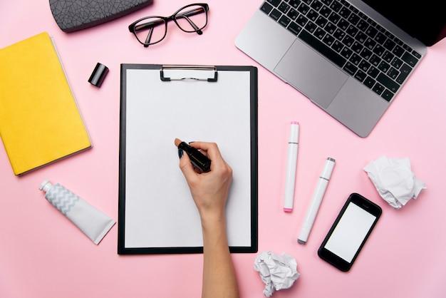 Vista superior da mesa de escritório rosa da mulher com laptop, telefone com tela branca, óculos, batom, creme e bolas de papel amassado. feminino mão escreve batom em uma folha de papel branca fundo. Foto Premium