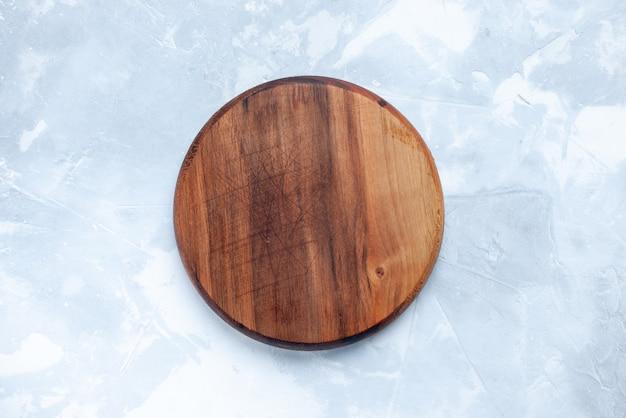 Vista superior da mesa de madeira marrom, redonda formada em uma mesa clara de madeira Foto gratuita
