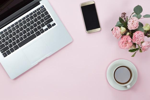 Vista superior da mesa de mesa de escritório rosa com laptop, smartphone, xícara de café e flores. copie o espaço, plana leigos. Foto Premium