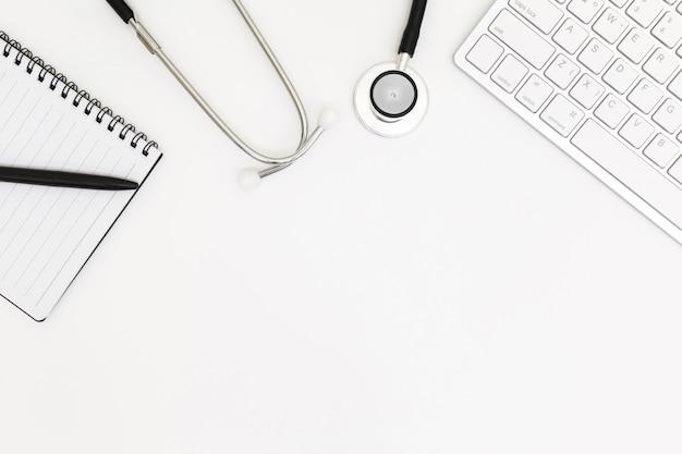 Vista superior da mesa de mesa do médico, papel em branco no branco Foto Premium