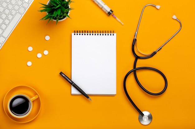 Vista superior da mesa de um médico com bloco de notas e caneta estetoscópio, teclado, prescrição e pílulas, uma xícara de café sobre um fundo amarelo Foto Premium