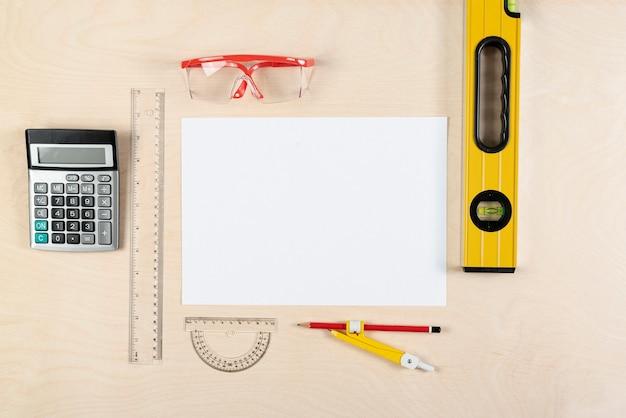 Vista superior da mesa do construtor com folha de papel em branco Foto gratuita