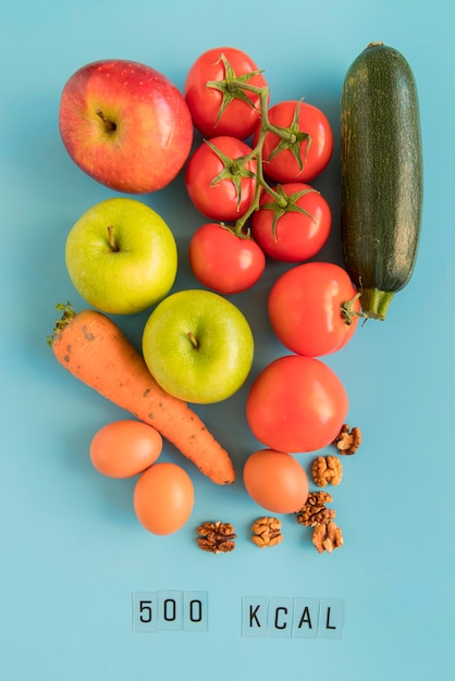 Vista superior da mistura de legumes e contagem de kcal Foto gratuita