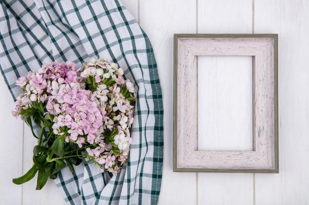 Vista superior da moldura branca com um buquê de flores em uma toalha verde xadrez em uma superfície branca Foto gratuita