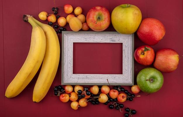 Vista superior da moldura cinza com bananas, groselha preta, maçãs, pêssegos e cerejas brancas em uma superfície vermelha Foto gratuita