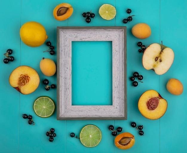 Vista superior da moldura cinza com damascos, maçãs e limão com groselha preta com fatias de limão em uma superfície azul clara Foto gratuita