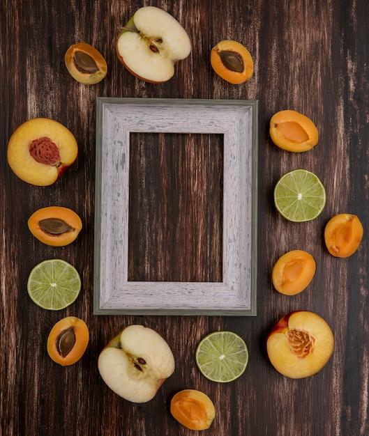 Vista superior da moldura cinza com fatias de limão, damascos de pêssego e maçã em uma superfície de madeira Foto gratuita
