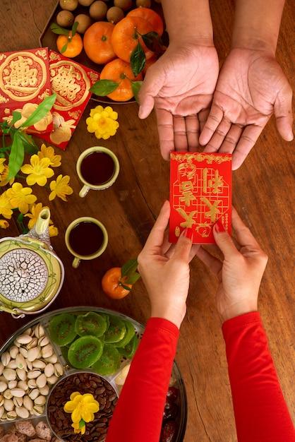 Vista superior da mulher cortada irreconhecível, entregando o presente do ano novo chinês ao homem Foto gratuita