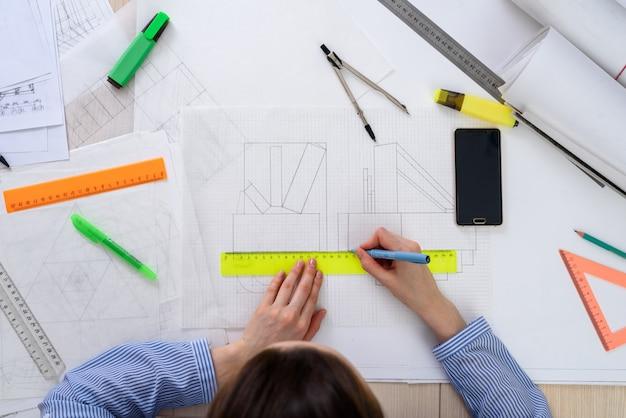 Vista superior da mulher do arquiteto no trabalho sobre o design do edifício, sobre o papel de mesa, réguas, lápis, bússola, smartphone, desenho torcido. Foto Premium