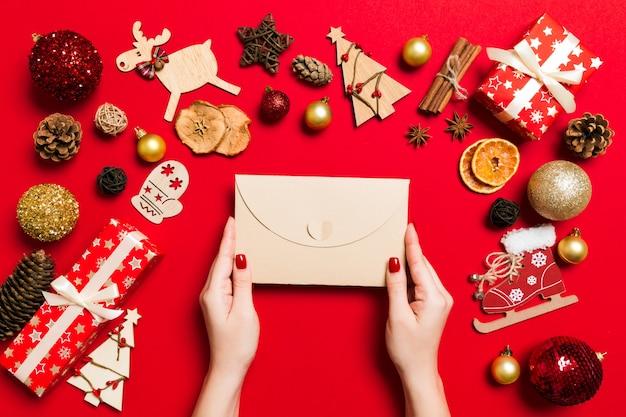 Vista superior da mulher segurando um envelope em fundo vermelho, feito de férias. conceito de tempo de natal Foto Premium