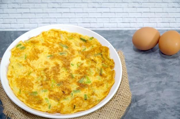 Vista superior da omeleta (omeleta, ovo mexido) com a cebola verde na tabela. estilo asiático. Foto Premium
