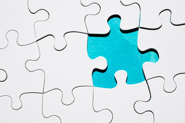 Vista superior da peça do quebra-cabeça faltando no cenário de grade de quebra-cabeça Foto gratuita