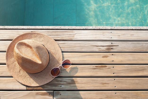Vista superior da piscina, chapéu de sol e óculos de sol no chão de madeira Foto Premium