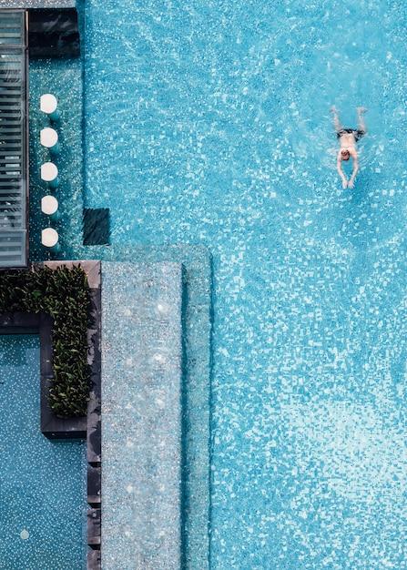 Vista superior da piscina com barra de flutuação e um homem que nada no verão. Foto Premium