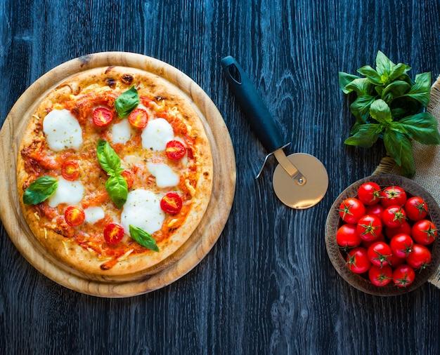 Vista superior da pizza italiana italiana margherita sobre uma mesa de madeira com coberturas Foto Premium