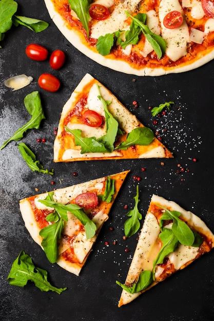 Vista superior da pizza na mesa de ardósia preta Foto gratuita
