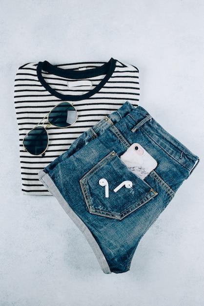 Vista superior da roupa feminina listrado t-shirt, shorts jeans e acessórios eadphones, smartphone. Foto Premium
