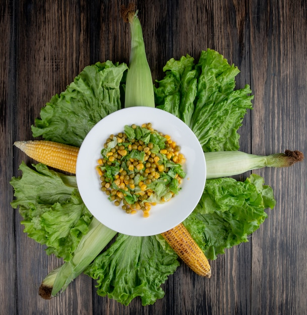 Vista superior da salada de milho com alface e ervilha verde com grãos na superfície de madeira Foto gratuita