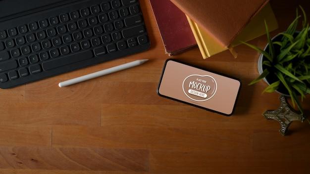 Vista superior da simulação da tela horizontal do smartphone na mesa de trabalho com tablet digital, notebooks e espaço de cópia Foto Premium