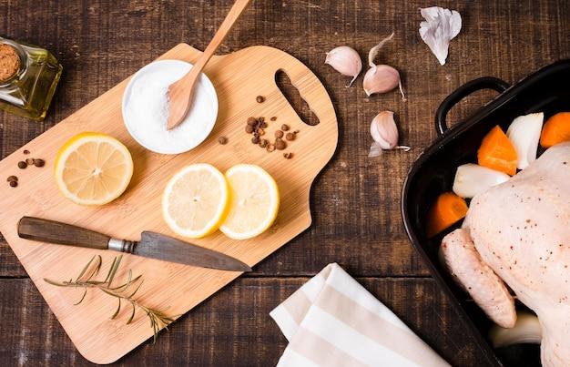Vista superior da tábua de cortar com rodelas de limão e frango Foto gratuita