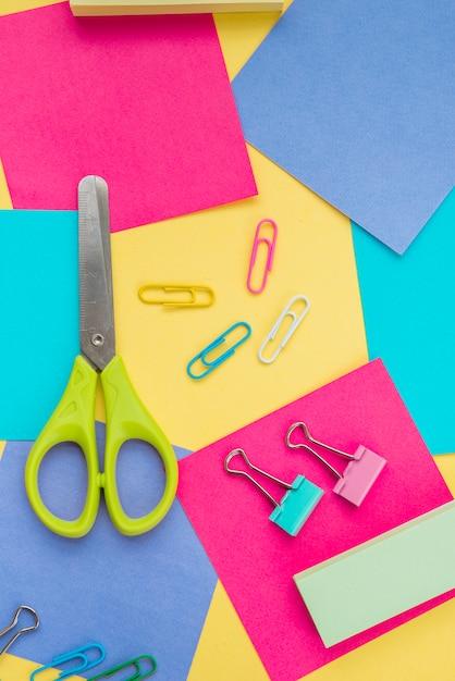 Vista superior da tesoura; clipe de papel e nota auto-adesiva colorida Foto gratuita