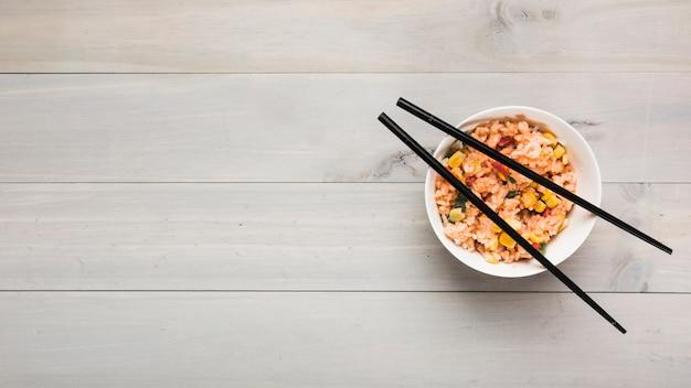 Vista superior da tigela de arroz frito chinês com pauzinhos pretos na mesa de madeira Foto gratuita
