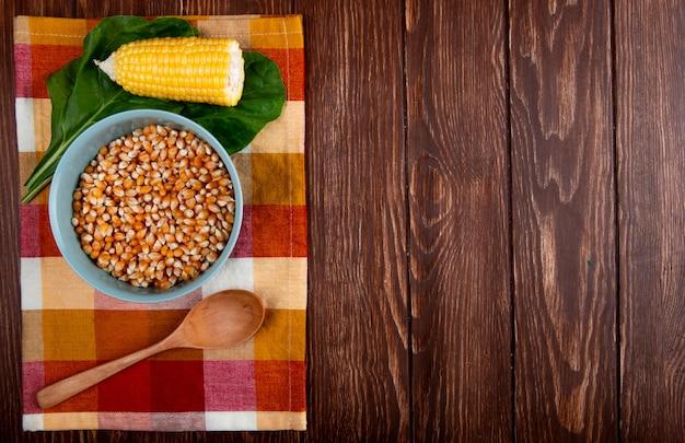 Vista superior da tigela de semente de milho seco com colher de pau de milho cozido e espinafre no pano e madeira com espaço de cópia Foto gratuita