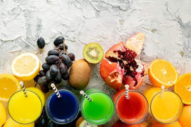 Vista superior da variedade de suco fresco, frutas diferentes ao redor, cópia espaço para o seu texto em uma tabelas pretas Foto Premium