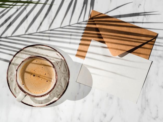 Vista superior da xícara de café e envelope Foto gratuita