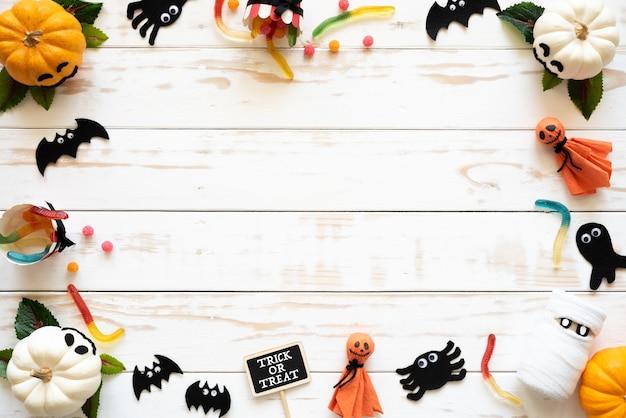 Vista superior das abóboras fantasma branco e amarelo, ofício de halloween em fundo branco de madeira Foto Premium