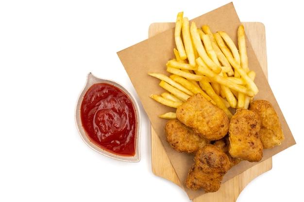 Vista superior das batatas fritas com pepitas e ketchup em um fundo branco. Foto Premium