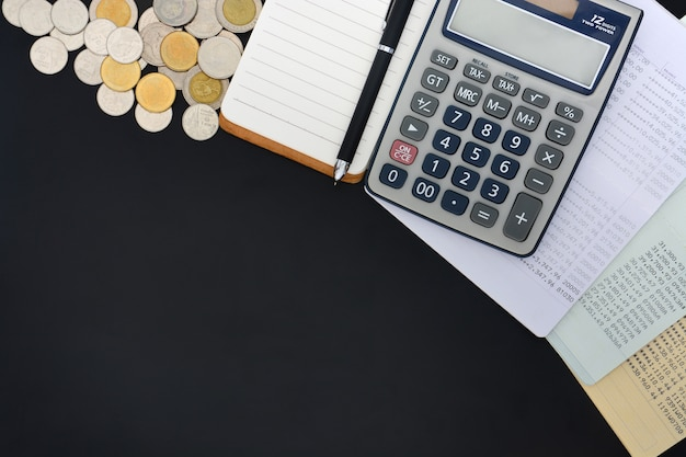 Vista superior das cadernetas de poupança conta, calculadora, bloco de notas e pilha de moedas em fundo preto Foto Premium
