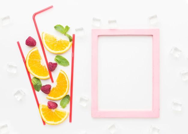 Vista superior das fatias de laranja em um copo de palha com hortelã e moldura Foto Premium