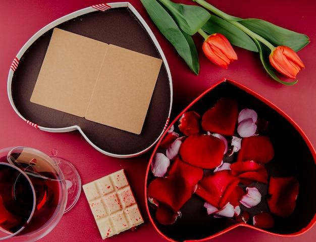 Vista superior das flores de tulipa de cor vermelha com caixa de presente em forma de coração com um cartão postal aberto e uma caixa cheia de pétalas de rosa e chocolate branco com um copo de vinho sobre fundo vermelho Foto gratuita