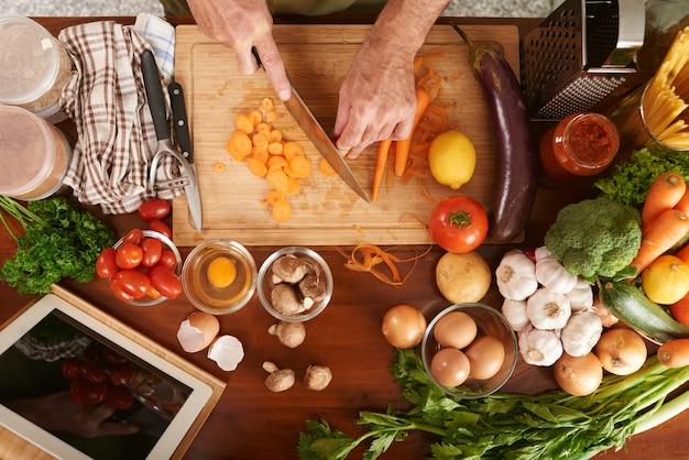 Vista superior das mãos cortadas de cozinheiro sênior irreconhecível corte cenoura cozinhar ensopado de legumes Foto gratuita