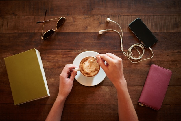 Vista superior das mãos cortadas mexendo cappuccino com óculos, livro, carteira e smartphone deitado em cima da mesa Foto gratuita