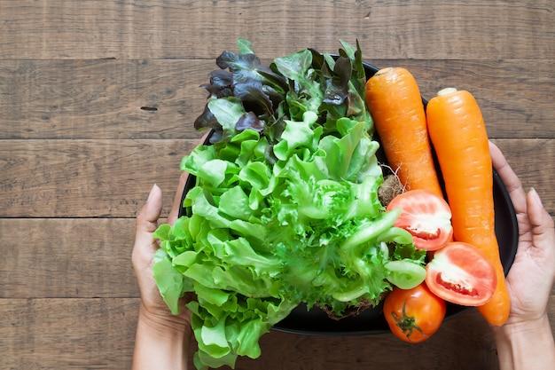 Vista superior das mãos da mulher segurando um prato de legumes frescos Foto Premium
