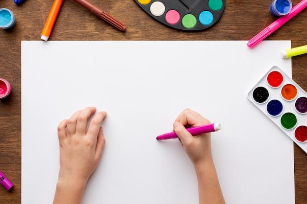 Vista superior das mãos de desenho em papel Foto Premium