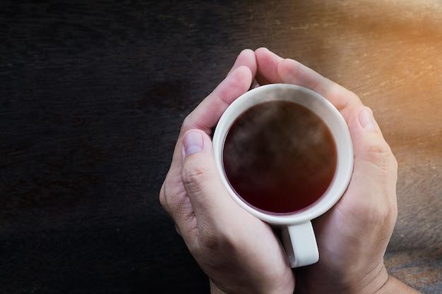 Vista superior das mãos de homem segurando quente caneca de café Foto gratuita