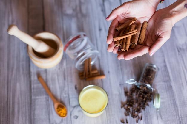 Vista superior das mãos de mulher com ingredientes na mesa, pilão de madeira, açafrão amarelo, cravo e folhas naturais verdes. de perto, durante o dia Foto Premium