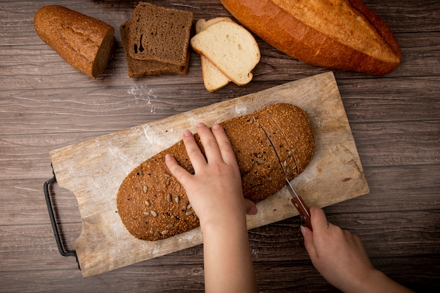 Vista superior das mãos de mulher cortando pão de sanduíche na tábua e outros pães em fundo de madeira Foto gratuita