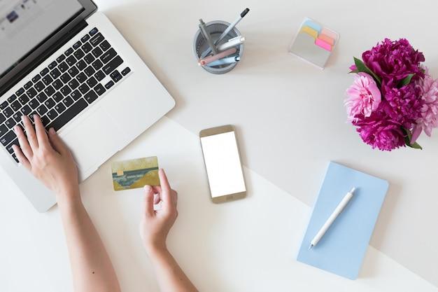 Vista superior das mãos de mulher segurando um cartão de crédito, conceito de compras on-line, espaço de trabalho com computador portátil, telefone celular, flores e notebook, configuração plana. Foto Premium