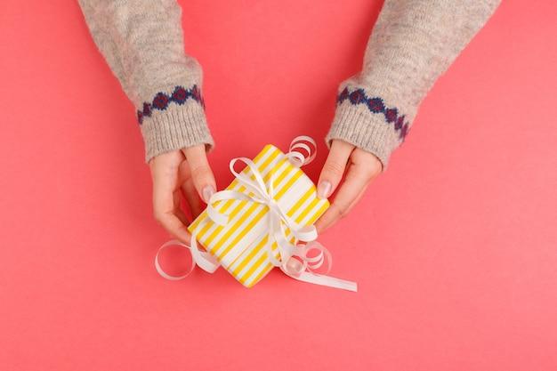 Vista superior das mãos de mulher segurando uma caixa de presente rosa Foto Premium
