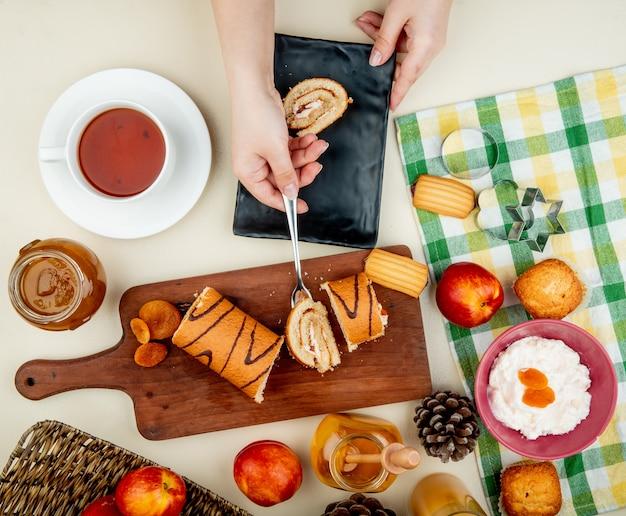 Vista superior das mãos de mulher segurando uma fatia de rolo com garfo na tábua com ameixas secas, pêssegos, compotas, queijo cottage, biscoitos e pinhas e chá ao redor na mesa branca Foto gratuita