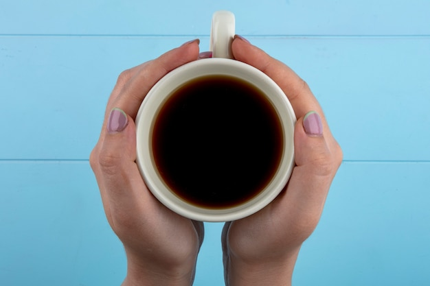 Vista superior das mãos de mulher segurando uma xícara de chá em fundo azul Foto gratuita