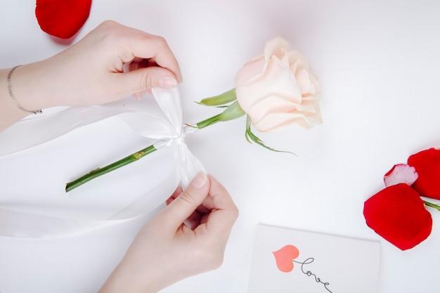 Vista superior das mãos femininas, amarrando um laço de fita branca em uma flor rosa em fundo branco Foto gratuita