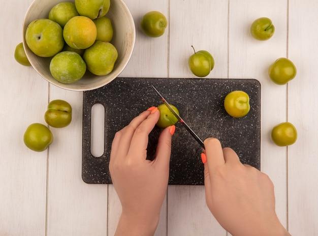 Vista superior das mãos femininas cortando ameixas verdes em uma tábua de cozinha com uma faca com ameixas verdes em uma tigela sobre um fundo branco de madeira Foto gratuita